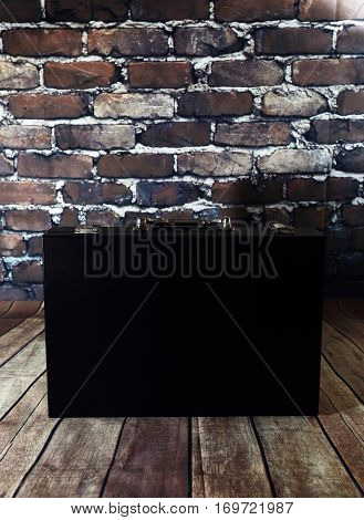 Black suitcase on brick wall background. Black case on wooden floor. Small suitcase for business papers