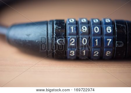 Unlocking the year 2017. 4 digit number combination lock with number 2017. Blue dial with white letters.
