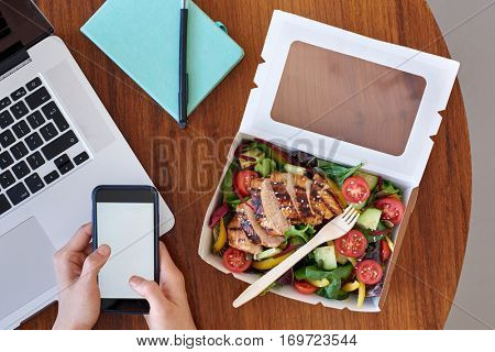 Overhead of work station, laptop computer with hands and takeout salad
