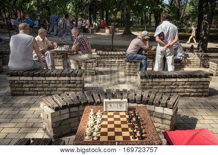 KIEV UKRAINE - AUGUST 17 2015: Old men playing chess in Taras Shevchenko Park kiev capital city of Ukraine