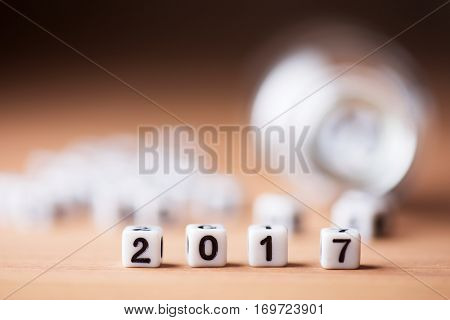 2017 aligned with white number cubes with black letters, spilling out from a small glass bottle, on a wooden desk top
