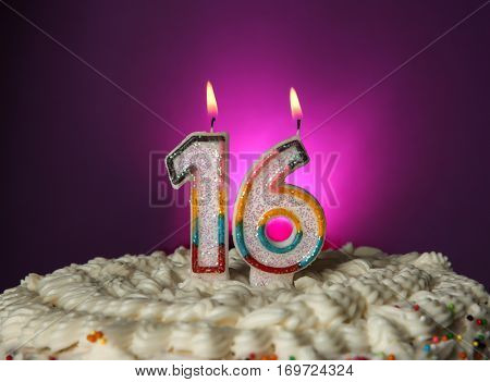 Tasty cake with candles for sixteenth birthday on purple background