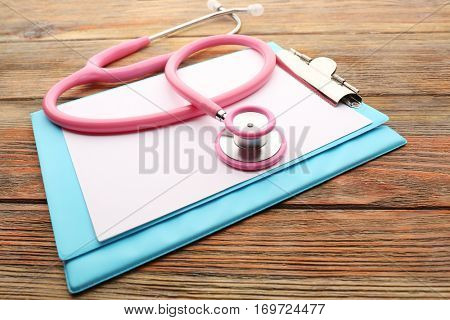 Pink stethoscope and folder on wooden background