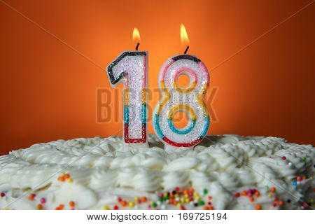 Tasty cake with candles for eighteenth birthday on orange background