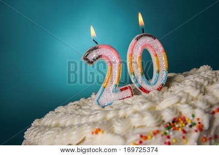 Tasty cake with candles for twentieth birthday on blue background
