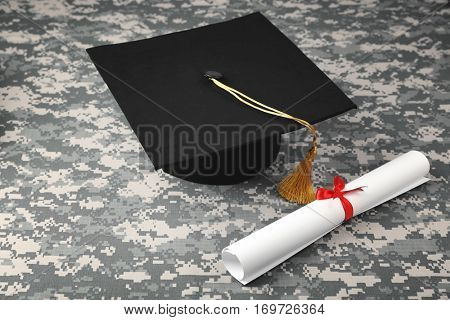 Graduation hat and diploma scroll on camouflage background