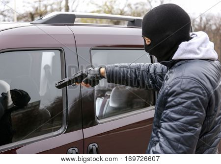 Male thief with pistol trying to steal car