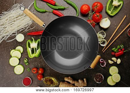 Empty wok pan with fresh ingredients and spices on dark background, top view