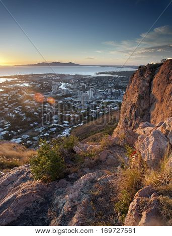 Overview of Townsville Queensland Australia from a lookout on a mountain peak over the rooftops of the city to the ocean beyond at sunset