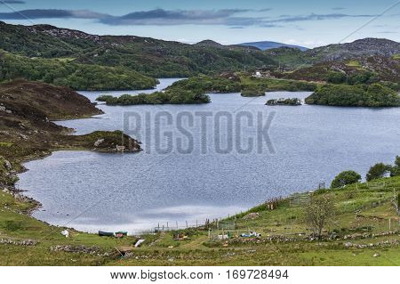 Assynt Peninsula Scotland - June 7 2012: Charming small lake with multiple green islands at Drumbeg hamlet. Blue sky green hills blue water some clutter on pasture.