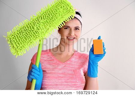 Happy young cleaner with dust mop and sponge on light background