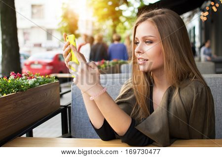 Portrait of a beautiful blonde woman that reads what is on your phone sitting in a modern cafe on a summer area an attractive girl hipster communicates with a mobile phone relaxing at lunchtime. The Internet.