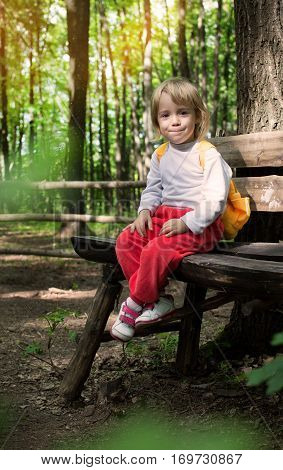 Little girl sitting on a bench in the park in the open air in anticipation of camping. Travel and adventure with your child. Cute little traveler with a backpack.
