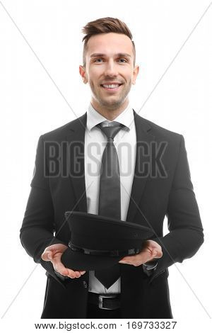 Young smiling chauffeur holding hat on white background