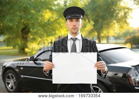 Young chauffeur standing with white board near luxury car on the street