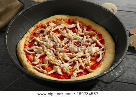Unbaked pizza in pan, closeup