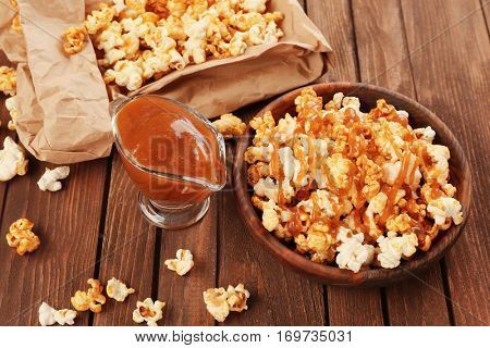 Bowl full of sweet popcorn and caramel sauce on wooden background