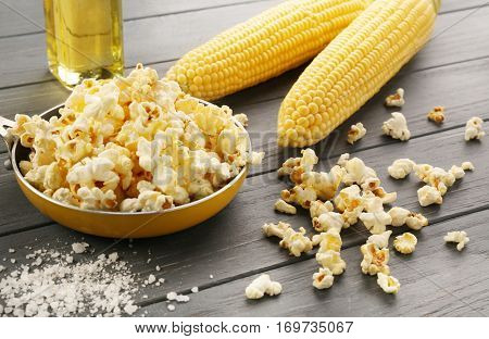 Frying pan with tasty traditional popcorn and corncobs on grey wooden background