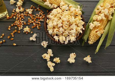 Bowl with tasty traditional popcorn and corncobs on grey wooden background