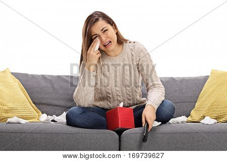 Sad young woman watching television on a sofa and crying isolated on white background