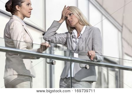 Young businesswoman arguing with female colleague at office railing