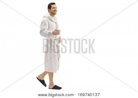 Full length portrait of a young man in a bathrobe holding a cup and walking isolated on white background