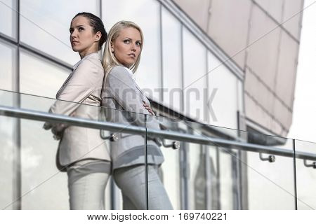 Serious young businesswomen standing back to back at office railing