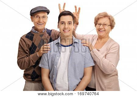 Cheerful seniors pranking a young man with bunny ears isolated on white background