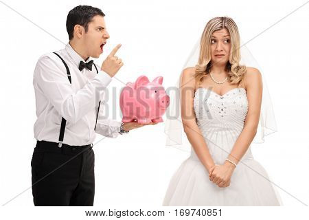 Angry groom holding a piggybank and scolding an embarrassed bride isolated on white background