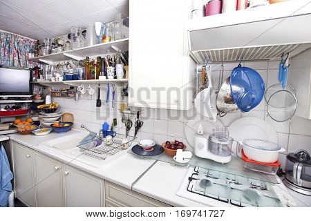 Interior of domestic kitchen with utensils and shelves