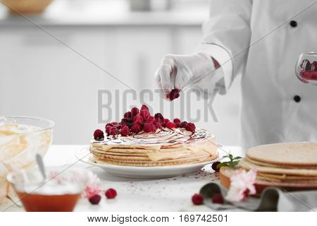 Cooking concept. Professional confectioner decorating tasty cake with fresh berries