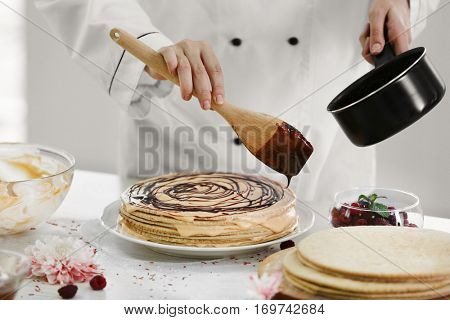 Cooking concept. Professional confectioner decorating tasty cake with chocolate frosting