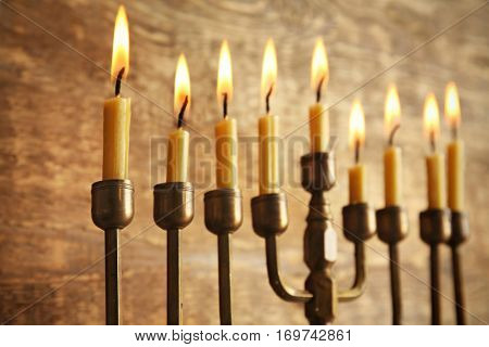 Menorah with candles for Hanukkah on wooden background, close up