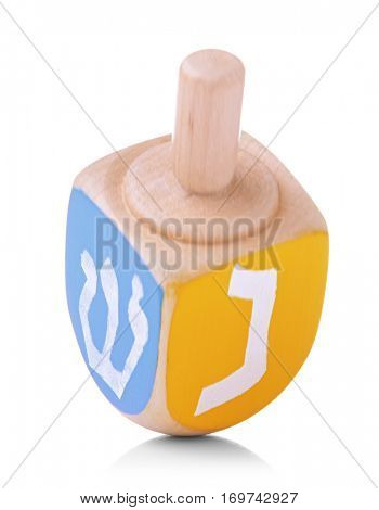 Wooden dreidel for Hanukkah on white background