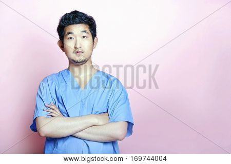Young Asian Trainee Doctor wearing Scrubs