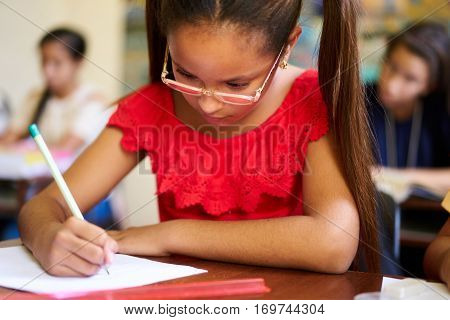 Young people and education. Group of hispanic students in class at school during lesson. Girl with paper for admission test examination