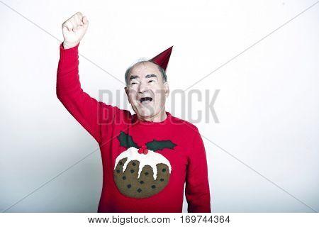 Senior adult man wearing Christmas jumper raising his arm in the air