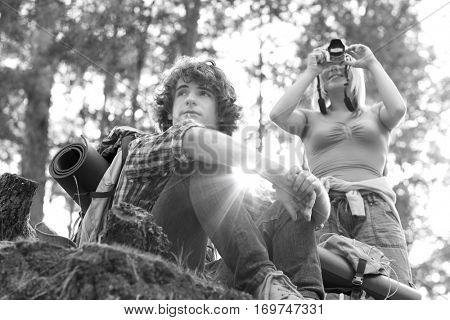 Young female hiker photographing through digital camera while man looking away in forest