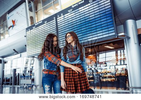 Two happy friends met at the airport.Art processing and retouching photos special.