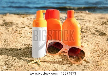 Sunscreen cream, sunglasses and starfish on sea coast