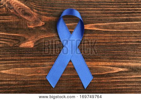Blue ribbon on wooden background. Colon cancer concept