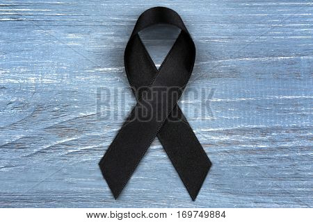Black ribbon on grey wooden background. Melanoma and mourning concept