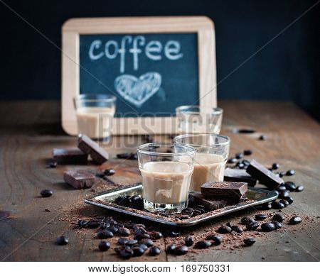 Shot glasses with homemade baileys roasted coffee beans and chocolate chalk board heart drawing love selective focus toned image