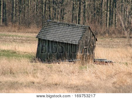 Old, abandoned shed sitting in a field
