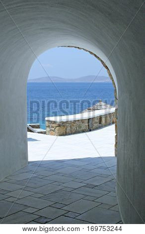 Looking through a white stone archway at the beautiful Aegean Sea