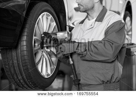 Midsection of male mechanic repairing car's wheel in workshop
