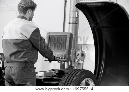 Rear view of mid adult automobile mechanic working in workshop