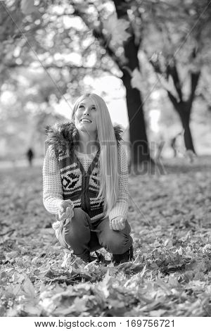 Young woman crouching while looking up in park during autumn