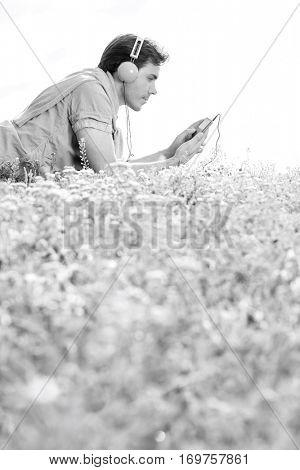Side view of man listening to music on MP3 player using headphones while lying in park against clear sky