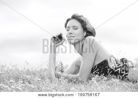 Side view of woman listening to music through MP3 player using headphones while lying on grass against sky
